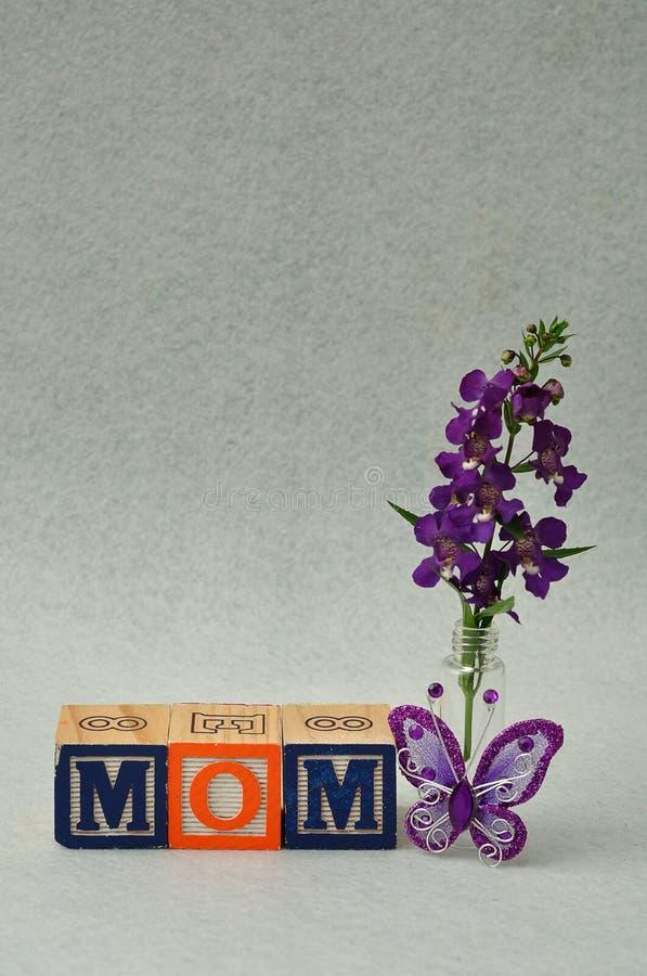 妈妈拼写了与字母表块和小紫色花 免版税库存图片