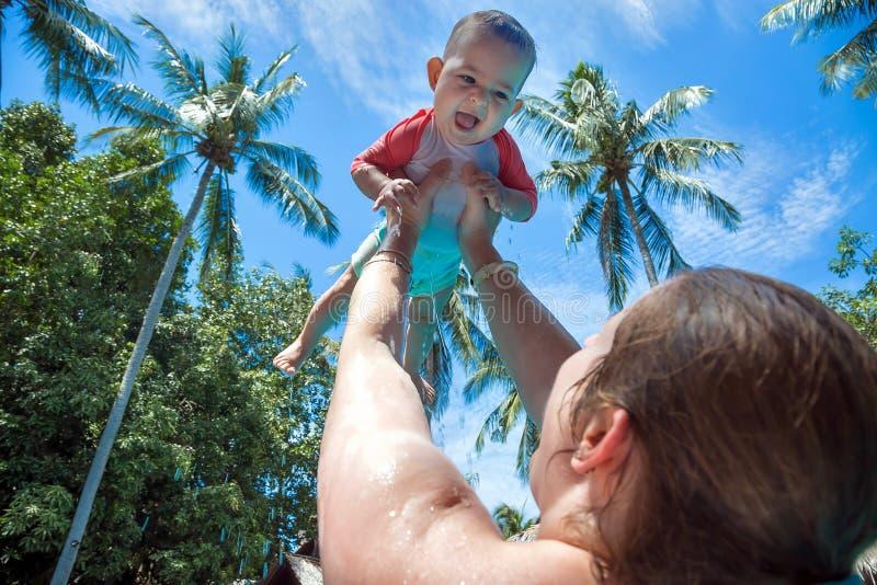 妈妈提高了在头上的儿童上流在水池 女孩是非常喜悦的愉快和尖叫 夏天休假,棕榈 库存照片