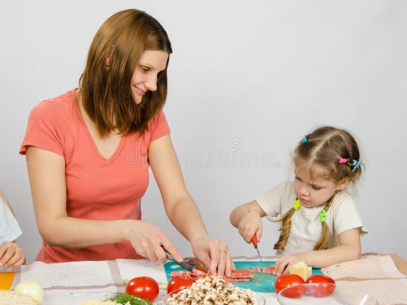 妈妈教女儿对与刀子产品的六年裁减烹调的在厨房用桌上 免版税图库摄影