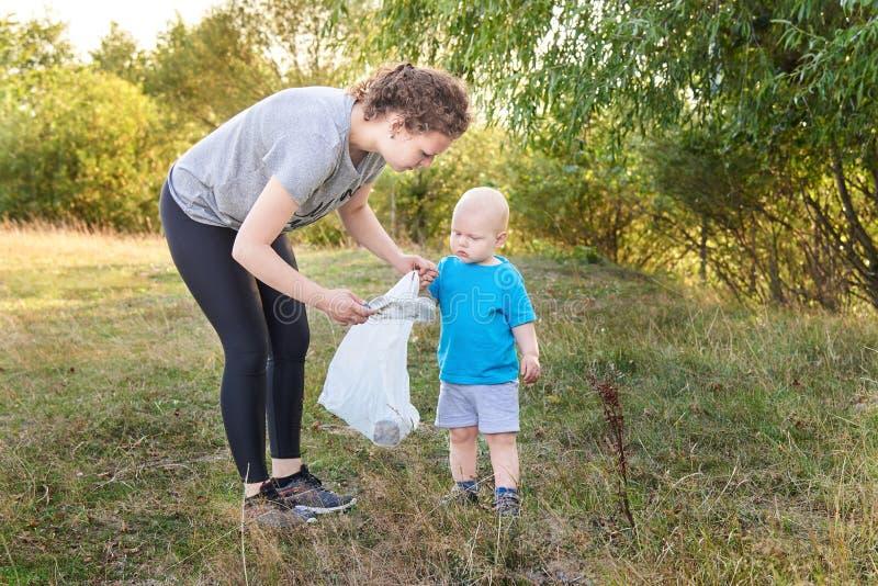 妈妈教她的儿子清扫垃圾本质上 环境污染题目由垃圾的 免版税库存照片