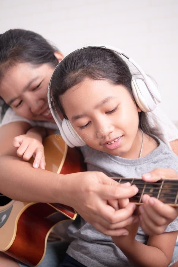 妈妈教她的女儿弹吉他 库存图片