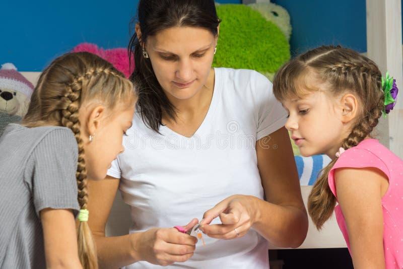 妈妈显示女儿如何删去从彩纸的手工纸 免版税库存照片