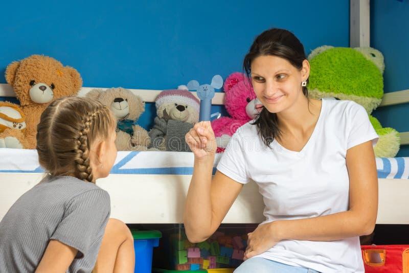 妈妈显示她的女儿在她的手指的自创小雕象 免版税图库摄影