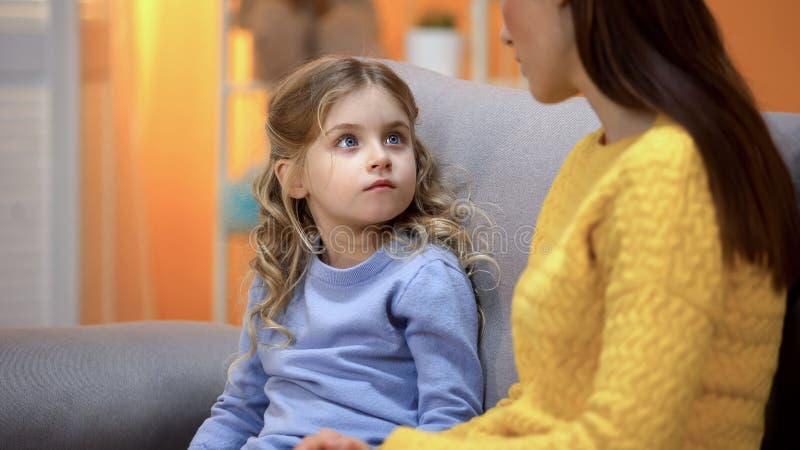 妈妈有与女孩的严肃的交谈,解释孩子差错在行为 库存图片