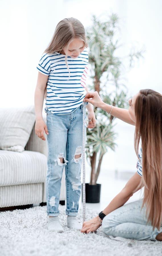 妈妈检查她的女儿的牛仔裤的长度 免版税库存图片