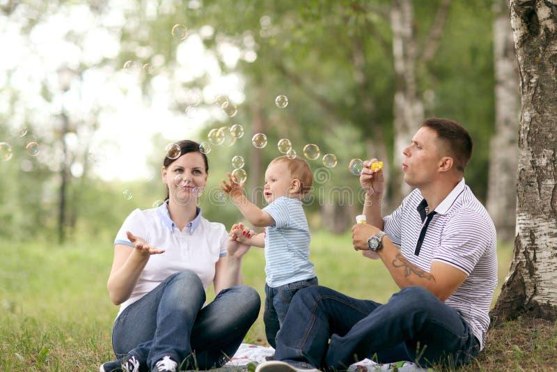 妈妈爸爸和婴孩在公园 图库摄影