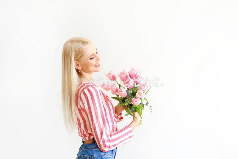 妈妈牛仔裤和郁金香庄稼顶面衬衣藏品花束的年轻白肤金发的妇女  免版税库存照片