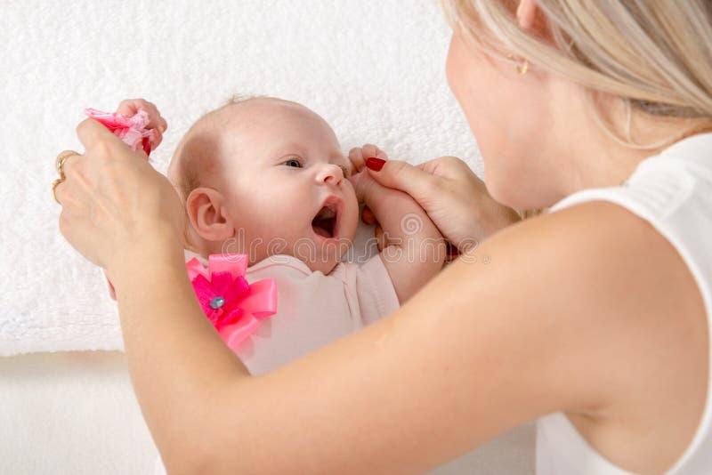 妈妈看有一张开放嘴的一个两个月女孩 免版税图库摄影