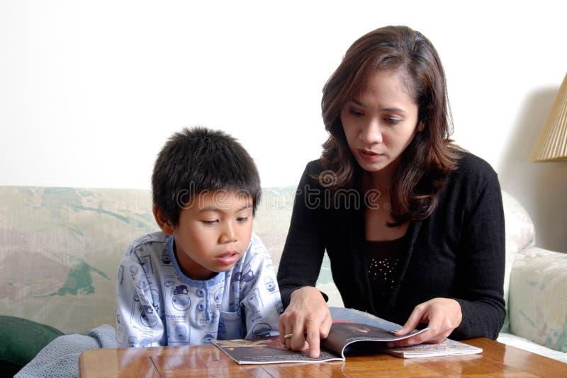 妈妈读取儿子 免版税库存图片