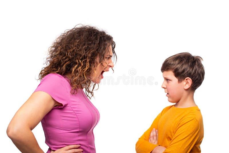 妈妈责骂少年的儿子,她对他情感地尖叫 对充电不满意的儿子 父母的问题和 免版税图库摄影