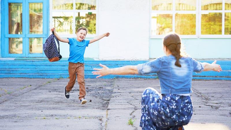 妈妈遇见她的从小学的儿子 快乐的儿童奔跑到他的母亲的胳膊里 一位愉快的男小学生跑往他的母亲 库存照片