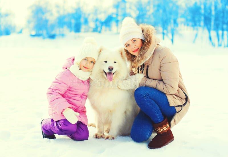 妈妈,小孩与白色萨莫耶特人狗冬天 免版税库存照片