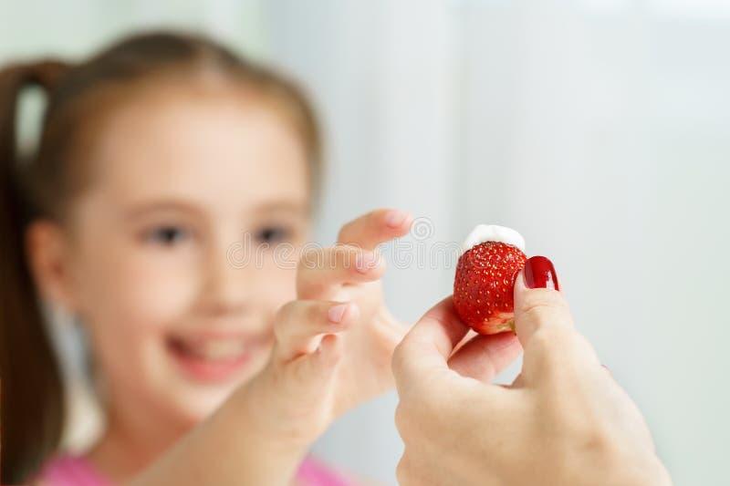 妈妈给与酸性稀奶油的成熟jucy草莓年轻逗人喜爱的微笑的小女孩 免版税库存图片