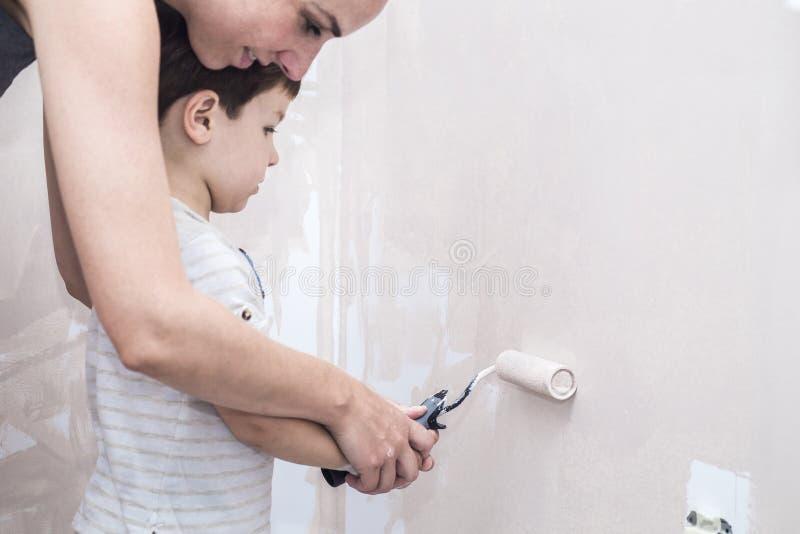 妈妈teachs她的3年与路辗的儿子绘画在家 免版税库存照片