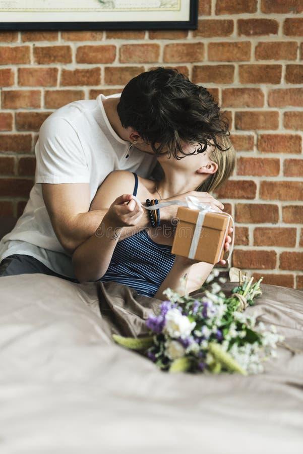 妻子从丈夫接受一个礼物盒和花花束  库存照片