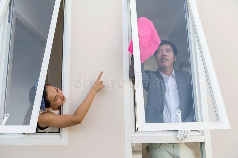 妻子清洗房子窗口的命令丈夫 库存照片
