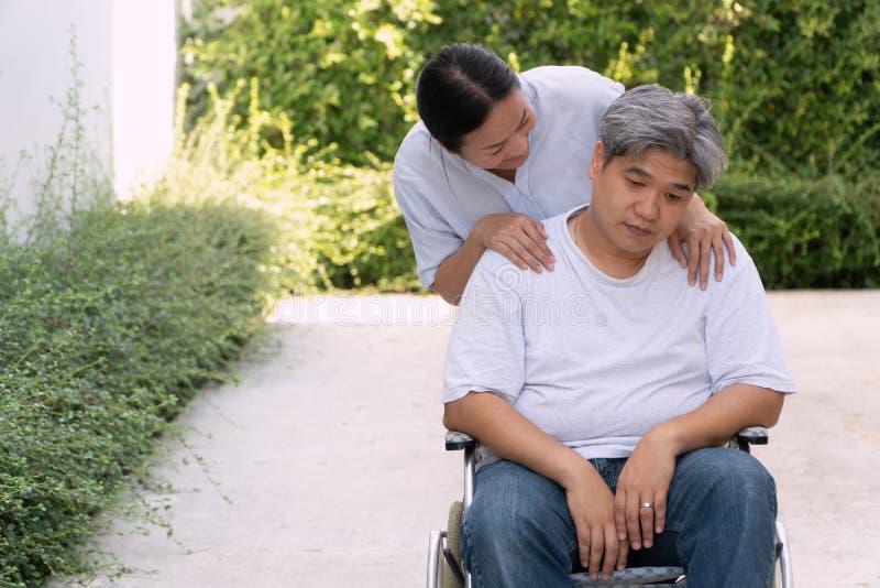 妻子照料是在轮椅的消沉丈夫 是怏怏不乐对于许多糖尿病,压力和的肥胖人民 免版税库存图片