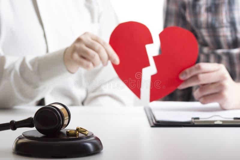 妻子,丈夫签署的离婚判决的手,溶解,取消婚姻,合法分居文件,归档 免版税库存图片