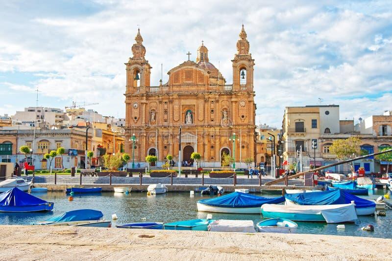 姆西达小游艇船坞的教区教堂有在马耳他岛的小船的 免版税库存照片