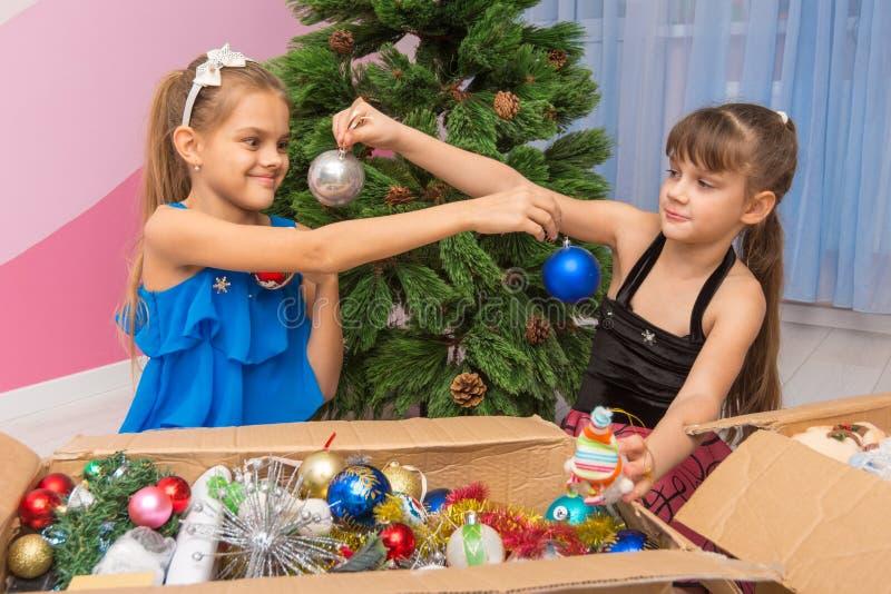 姐妹互相显示圣诞节球 免版税库存照片