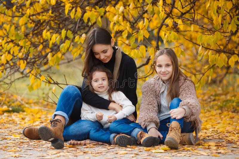 姐妹家庭画象在黄色秋天公园 库存照片