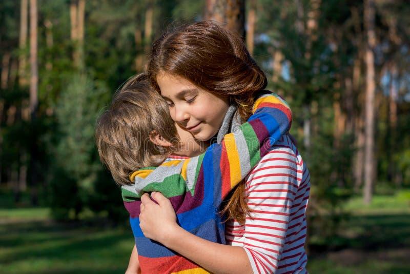 姐妹拥抱她的弟弟 免版税库存图片