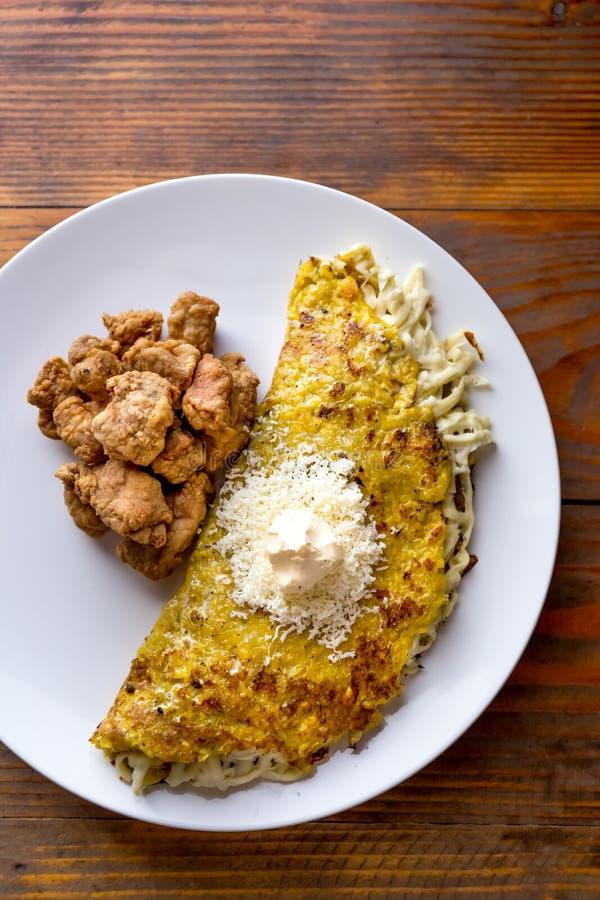委内瑞拉食物 玉米CACHAPA用乳酪和油煎的猪肉- cochino frito 木背景,顶视图 免版税图库摄影