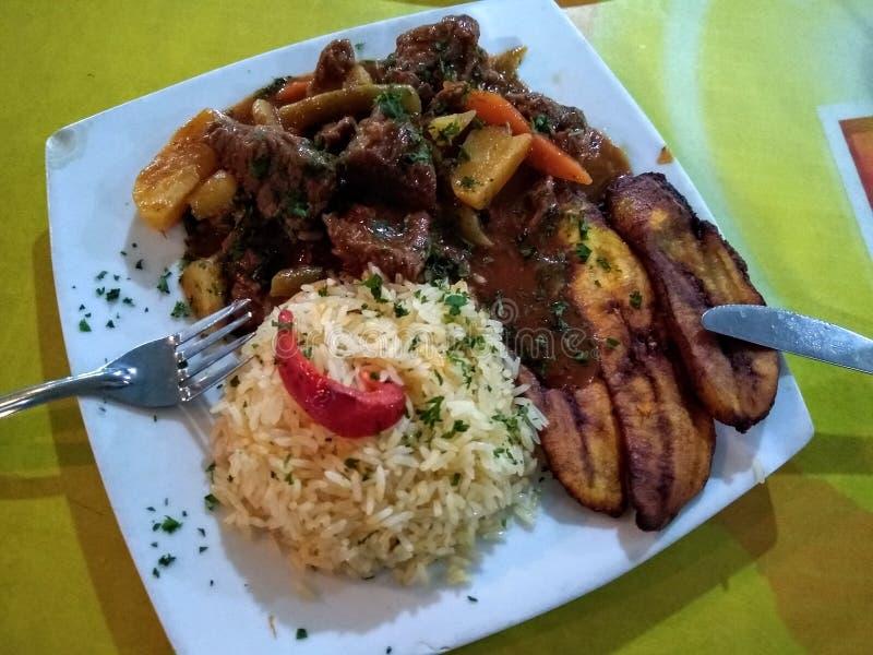 委内瑞拉食谱与春天菜、米和油煎的大蕉的焖肉 免版税库存照片