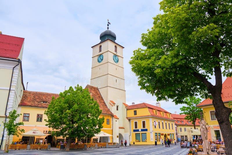 委员会塔Turnul Sfatului在锡比乌,看见从主要大正方形,与绿色树在阴暗天 免版税库存图片