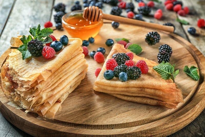 委员会用鲜美稀薄的薄煎饼和莓果 库存图片