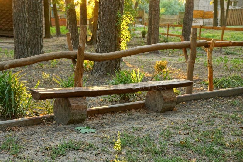 从委员会的在篱芭附近的长木凳和日志在一个法院围场 免版税图库摄影