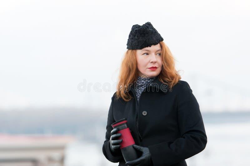 姜妇女画象黑外套和帽子的有红色嘴唇的 拿着热水瓶的妇女画象 有杯子的红色头发夫人在手上 免版税库存图片