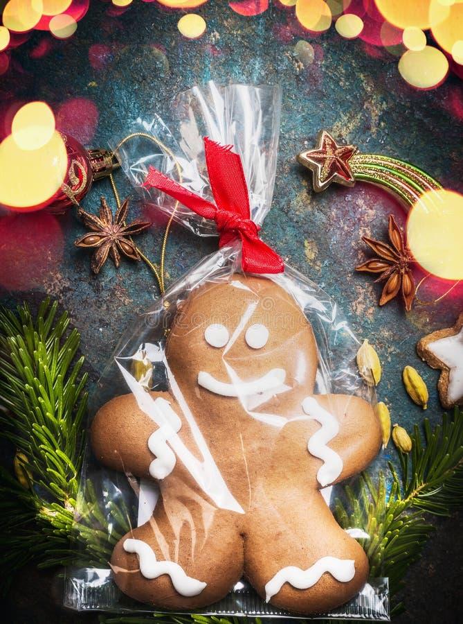 姜饼人曲奇饼包裹在玻璃纸袋子和栓与在葡萄酒背景的欢乐丝带与假日bokeh照明设备 图库摄影
