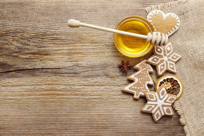 姜饼圣诞节曲奇饼和碗在木桌上的蜂蜜 免版税库存照片