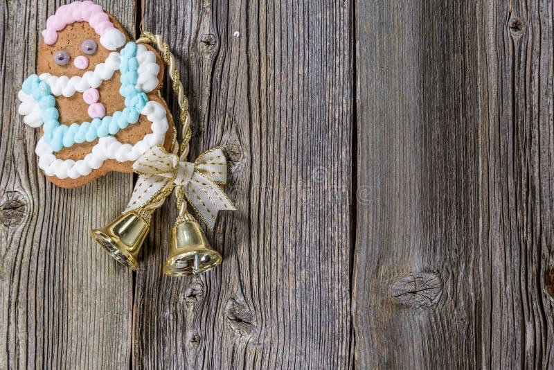 姜饼曲奇饼和响铃在老木头 免版税库存照片