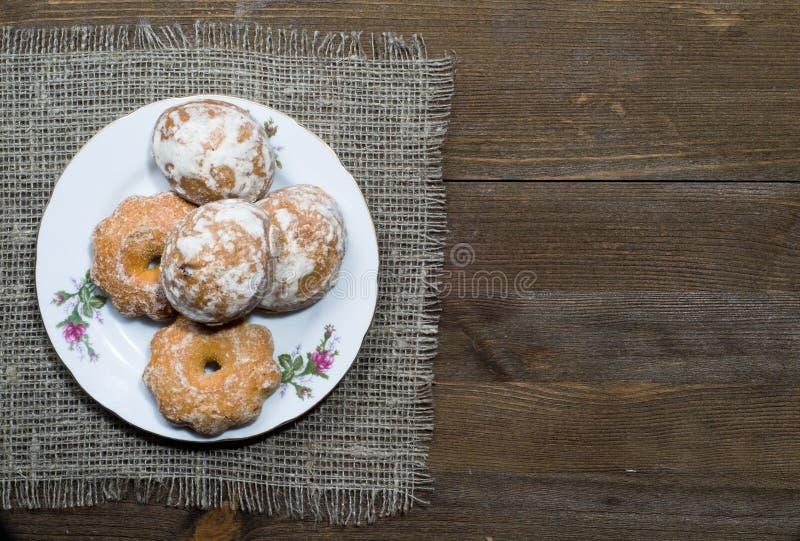 姜饼曲奇饼在一个木倾斜在背景中安排了 免版税库存照片