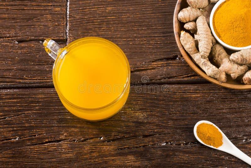 姜黄和水,健康饮料-木背景 图库摄影