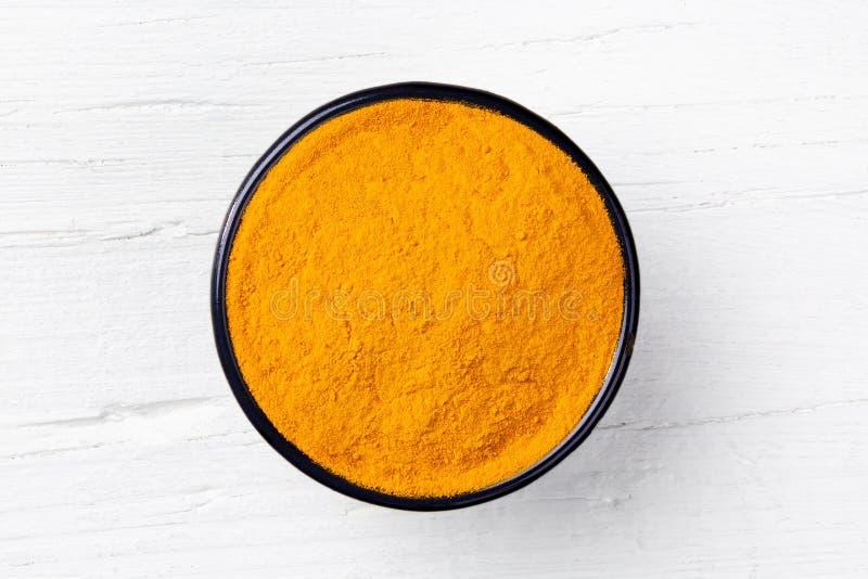 姜黄在白色木背景的姜黄粉末 免版税库存照片