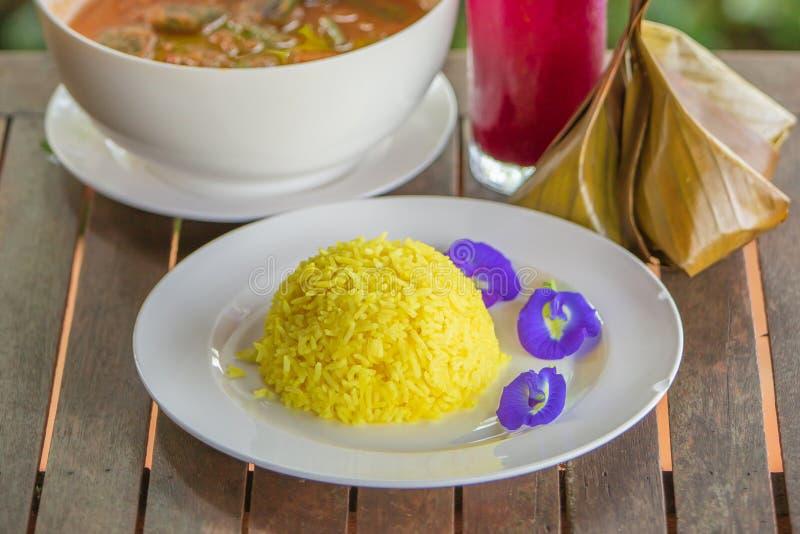 姜黄在白色板材的米和蝴蝶豌豆 在一张木桌上的传统泰国食物 泰国的样式 领域浅dept 关闭 免版税库存照片