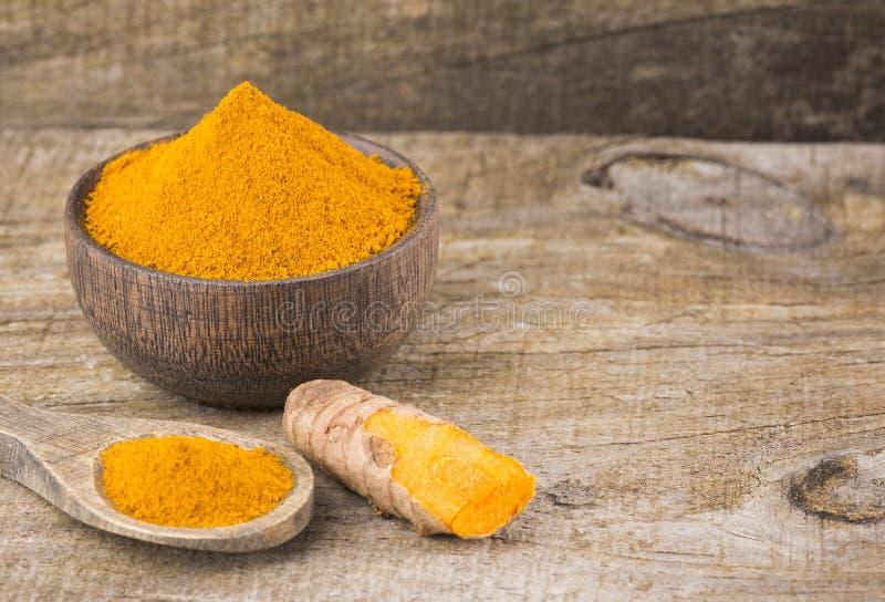 姜黄粉末和新鲜的姜黄在木背景-姜黄longa 免版税库存照片