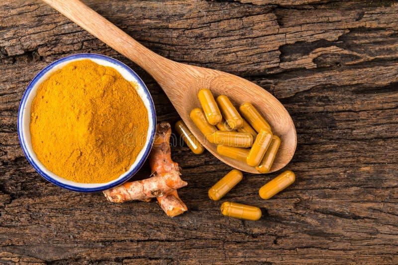 姜黄粉末、胶囊和根姜黄素在木板材 库存图片