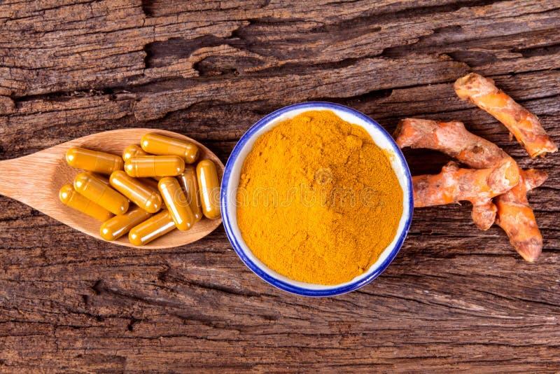 姜黄粉末、胶囊和根姜黄素在木板材 库存照片
