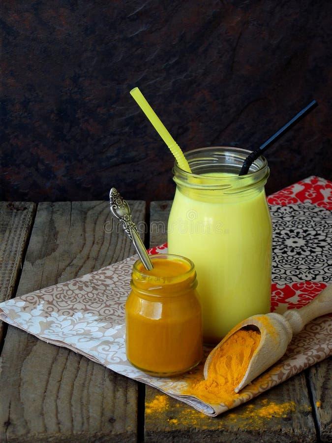 姜黄粉末、酱和拿铁在木背景 Ayurvedic健康金黄饮料用椰奶和酥油秀丽和他的 库存图片