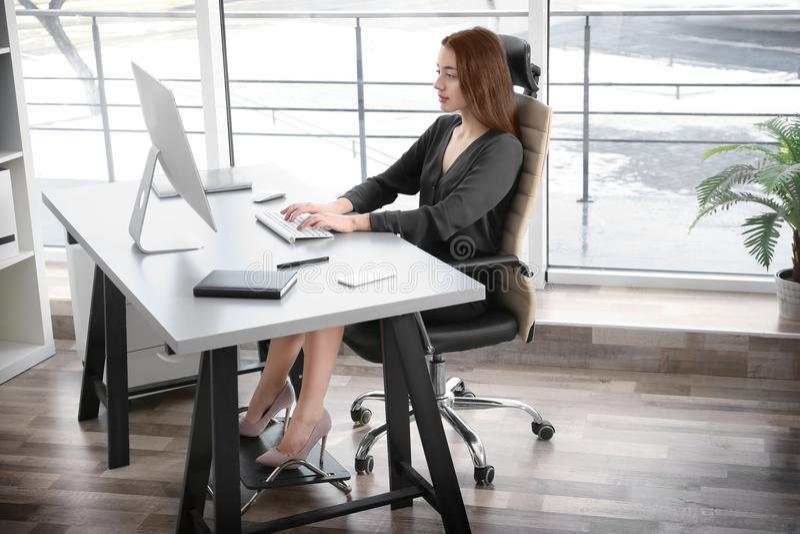 姿势概念 少妇与c omputer一起使用在办公室 免版税库存照片