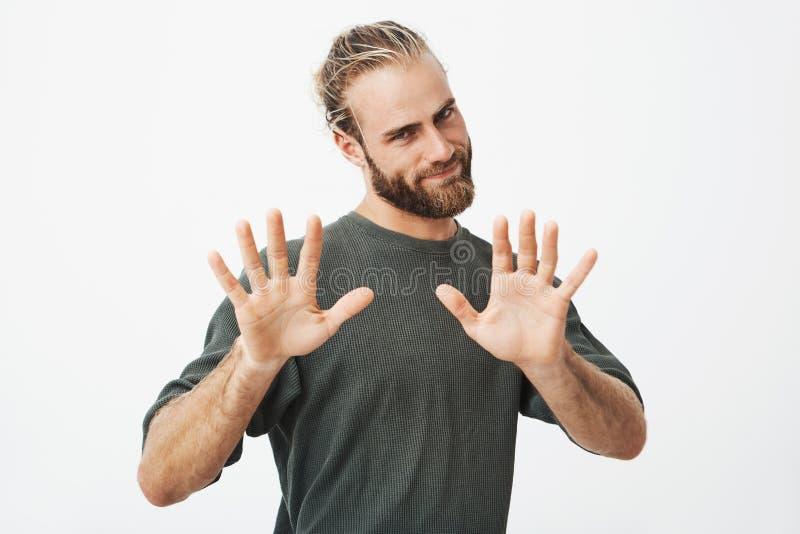 姿势示意用两只手的美丽的年轻人和胡子画象有时髦理发的,显示十个手指与 免版税库存照片