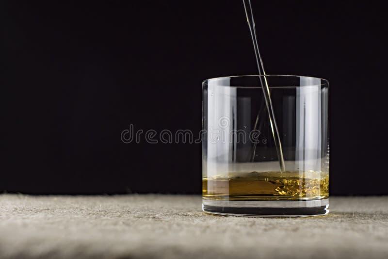 威士忌倒进玻璃杯里 库存照片