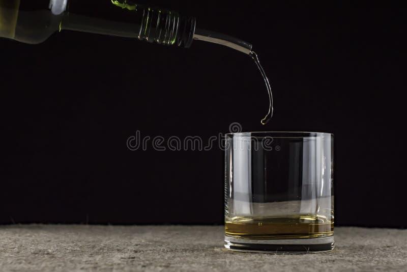 威士忌倒进玻璃杯里 免版税库存图片