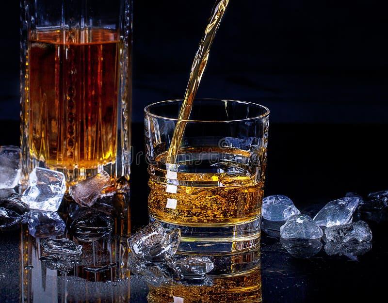 威士忌倒进玻璃杯 库存图片