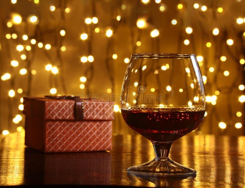 威士忌酒、科涅克白兰地、白兰地酒和礼物盒在木桌上 在轻的背景的庆祝构成 免版税库存图片