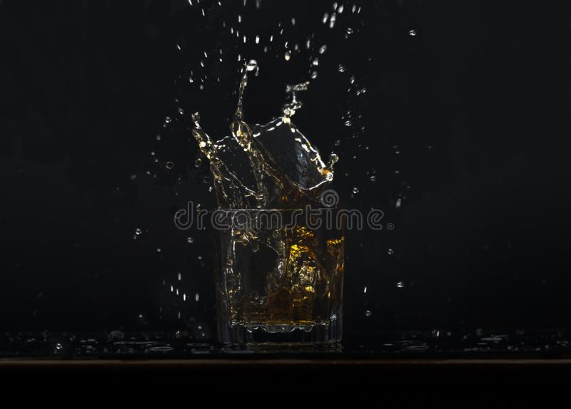 威士忌酒准备与落入玻璃的冰块,飞溅液体 免版税库存照片